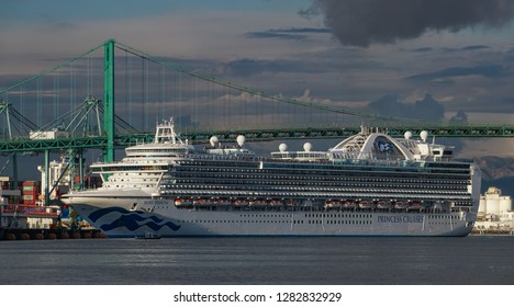 Los Angeles, California USA - January 12, 2019: Ruby Princess cruise ship turns in Port of Los Angeles in front of Vincent Thomas suspension bridge, dramatic sky and clouds, heading out to sea.
