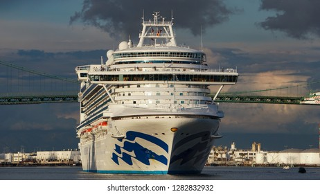 Los Angeles, California USA - January 12, 2019: Ruby Princess cruise ship in a front view in Port of Los Angeles harbor main channel heads toward open ocean, Vincent Thomas suspension bridge behind it