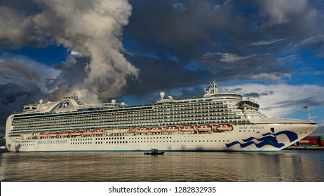 Los Angeles, California USA - January 12, 2019: Ruby Princess cruise ship en route toward the ocean in the Port of Los Angeles under a dramatic sky, 951 feet long.