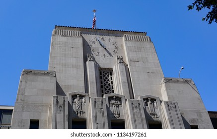 Los Angeles, California USA - July 14, 2018: Upper portion of Los Angeles Times newspaper building shows details of the Art Deco limestone sculptures and clock at the top of the tower.