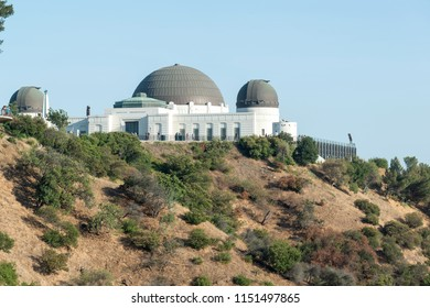Los Angeles, California, USA - July 16th 2018: Famous Griffith Observatory museum building on the Hollywood Hills. Many tourists visiting planetarium with scenic city landscape views.