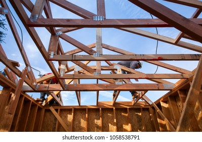 Los Angeles, California USA. March 19, 2018. New construction modern home with construction worker working on the installation of roof framing as part of the framing process