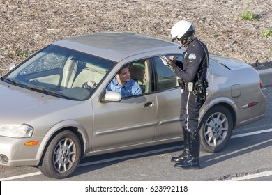 Los Angeles, California, USA - March 10, 2010: Los Angeles Police Department Police officer issuing a driver with a citation (ticket) for driving offences.