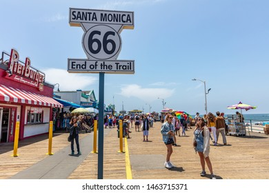 Los Angeles California USA. May 30, 2019. Santa Monica pier and Route 66 End of the trail, white color  sign. People walking at pier, blue sky background