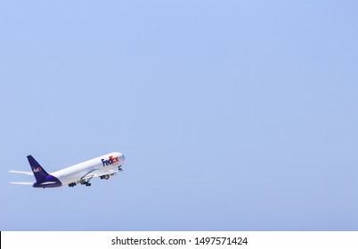 LOS ANGELES, CALIFORNIA, USA - MAY 22, 2019: A FedEx Cargo Boeing 767 takes off from Los Angeles International Airport (LAX). The machine is flying in the blue sky.