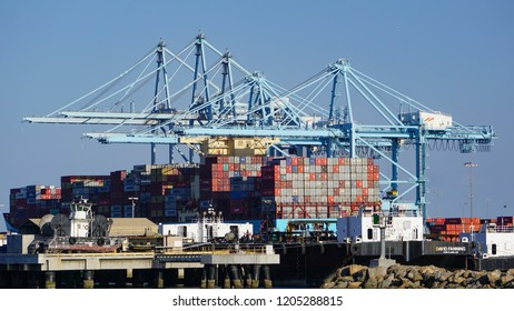 Los Angeles, California USA - October 13, 2018: Container ship being loaded in a modern industrial shipping harbor operation with a row of gantry cranes, surrounded by other port and ocean vessels.