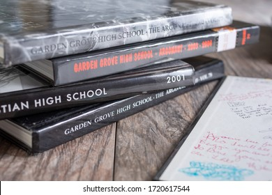Los Angeles, California/United States - 04/30/2020: A view of several high school yearbooks, on a wooden surface.