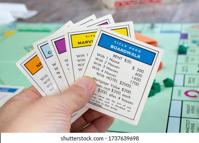 Los Angeles, California/United States - 05/07/2020: A view of a hand holding several property cards, part of the Monopoly board game.