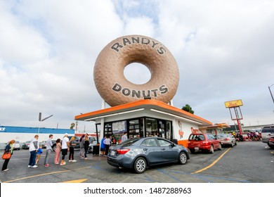 Los Angeles, California/United States - 07/19/2019: Several cars and people wait in line to order sweet treats from Randy's Donuts