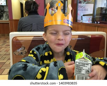 LOS ANGELES, CALIFORNIA/UNITED STATES – DEC 28, 2014: Little boy wearing Batman rob and Burger King crown smiles while drinking orange juice at a Burger King in Los Angeles, California.