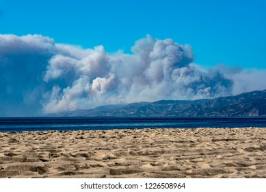 LOS ANGELES, CALIFORNIA/USA - November 9, 2018: The Woolsey Fire burns in Malibu from the Pacific Ocean into the Santa Monica mountains. Forest fire creates massive clouds of smoke.