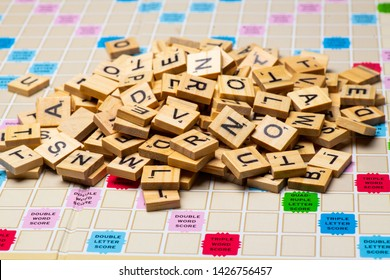 Los Angeles, CA/USA 06/16/2019 Heap of scrabble tile letters from above full frame over a scrabble board