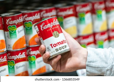 Los Angeles, CA/USA 4/10/2019 Customer hand holding a tin can of Campbells Brand Tomato soup in a supermarket aisle