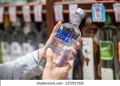 Los Angeles, CA/USA 4/10/2019 Customer hand holding A bottle of Absolut brand vodka in a liquor store aisle