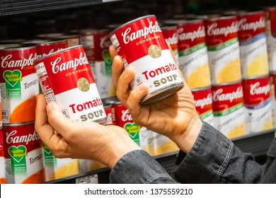 Los Angeles, CA/USA 4/15/2019 Customer hand holding two tin cans of Campbells Brand Tomato soup in a supermarket aisle