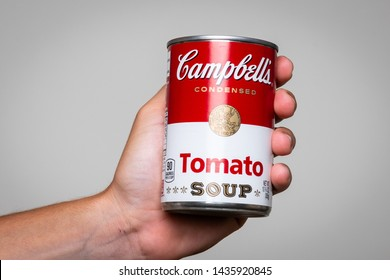 Los Angeles, CA/USA 6-21-2019 Human hand holding a tin can of Campbell's Soup tomato soup on gray background