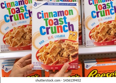 Los Angeles, CA/USA 6-21-2019  Shoppers hand holding a  package of General MIlls Cinnamon Toast Crunch brand  Wheat and rice cereal in a supermarket aisle