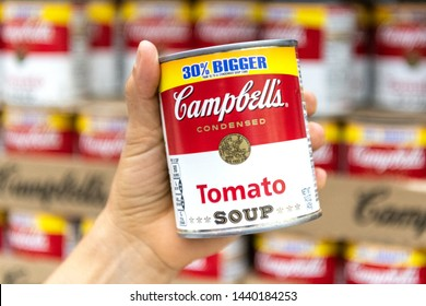 Los Angeles, CA/USA 7-1-2019  Shoppers hand holding a tin can of Campbells Brand Tomato soup in a supermarket aisle
