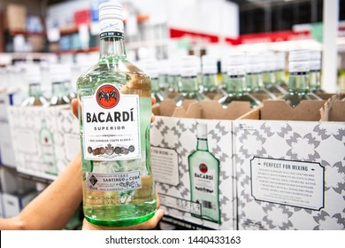 Los Angeles, CA/USA 7-1-2019  Shoppers hand holding a Bottle of Bacardi Carta Blanca Superior Brand White Rum in a supermarket aisle
