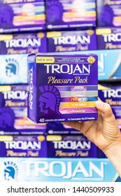 Los Angeles, CA/USA 7-1-2019 Shoppers hand holding a package of assorted Trojan brand condoms in a supermarket aisle