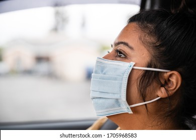 Los Angeles, Ca/USA - April 20, 2020: Woman wearing a surgical face mask while in the car. Local city orders, people must cover their face while outside of their homes to stop the spread of COVID-19