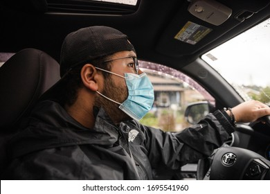 Los Angeles, Ca/USA - April 5, 2020: A millennial wearing a medical face mask while driving. Wearing recommended face mask during the coronavirus outbreak and global pandemic