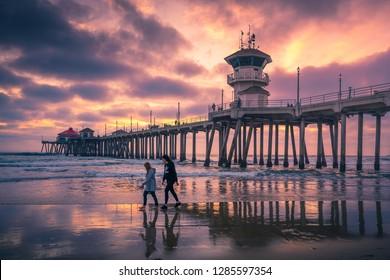 LOS ANGELES, CA/USA - JAN 11, 2019:  People walking along the beach at sunset near Huntington Beach Pier in Los Angeles, California