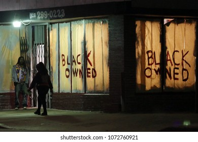 Los Angeles, CA/USA; July 16, 2013; People walk past a business on Crenshaw Blvd with the sign 'Black Owned' in the windows. Protests over the Zimmerman acquittal continued in Leimert Park all night.