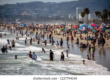 LOS ANGELES, CA/USA - July 4th, 2018: Great weather on 4th of July leads to very crowded beaches in Southern California. Beach umbrellas cover the sand as people escape the heat swimming in the ocean