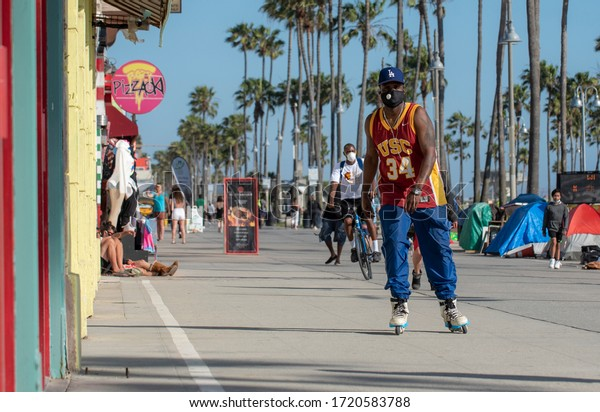 Los Angeles, CA/USA - May 2, 2020: Man wears face mask to protect from coronavirus infection while roller blading on famous Venice Beach boardwalk. Facemasks are new normal for L.A. residents.
