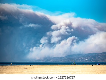 Los Angeles, CA/USA - November 9, 2018: View of Woolsey Fire as it burns Malibu, Ca from Pacific Ocean to Santa Monica Mountains. Billowing smoke clouds engulf coastline and blow into blue sky.