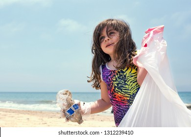 Los Angeles, CA/USA-circa 2015: little girl with trash bag cleaning up the beach