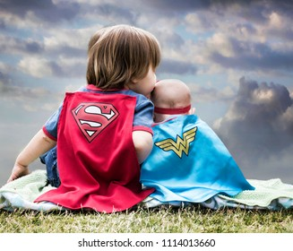 Los Angeles, CA/USA-May 2018: A little boy and his little sister dressed as superheros sit next to each other