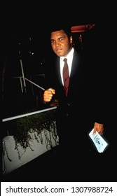 "Los Angeles - circa 1991: Muhammad Ali mugs for photographers leaving Spago restaurant. He holds a brochure ""Introducing Islam to non-Moslems""  """