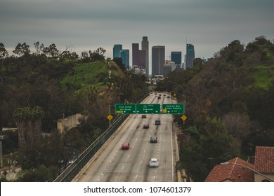 Los Angeles Cityscape overlooking all of downtown buildings, sunset light onto the 110 freeway with light LA traffic. To the right is Dodger Stadium exit for baseball.