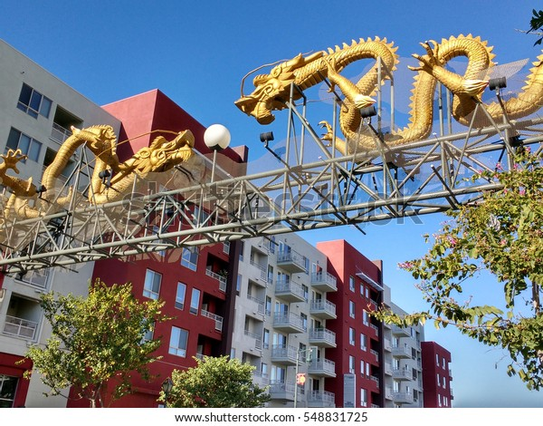 LOS ANGELES, DEC 17, 2016: The traditional Chinese dragon gate above Broadway stands in stark contrast to the newly built, modern apartment building behind it.