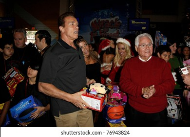 """LOS ANGELES - DEC 19: Arnold Schwarzenegger [asses out toys at the Hollenbeck Youth Center's 28th """"Miracle on 1st Street"""" with the LA Inner-City Games & Oscar de la Hoya Foundation in Los Angeles,CA on December 19, 2009."""