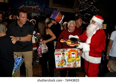 """LOS ANGELES - DEC 19: Arnold Schwarzenegger passes out toys at the  Hollenbeck Youth Center's 28th """"Miracle on 1st Street"""" with the LA Inner-City Games & Oscar de la Hoya Foundation in Los Angeles, CA on December 19, 2009."""