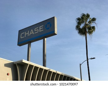 LOS ANGELES, DEC 22ND, 2017: Low angle, medium shot of Chase bank sign against a blue sky with clouds and a palm tree.