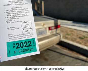 LOS ANGELES, DEC 26th, 2020: DMV California registration tags 2022 sticker, attached to renewal notice, close up next to back of golden Toyota car and license plate in a residential neighborhood.