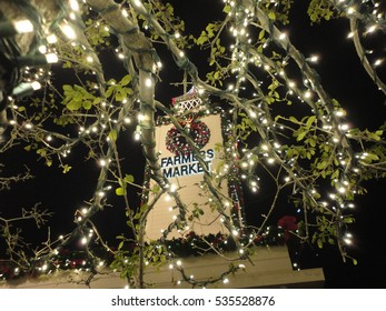 LOS ANGELES, DEC 3RD, 2016: Low angle shot of the historic clock tower at the Farmers' Market at Fairfax at the Grove, seen through the bright branches of a trees' Christmas lights during the holidays