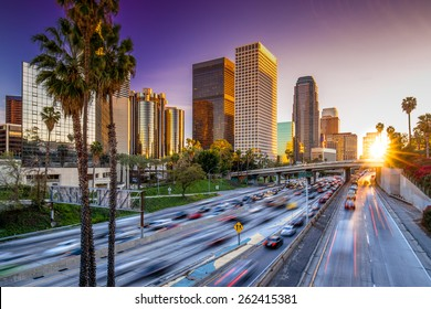 Los Angeles downtown buildings and highway car traffic at sunset