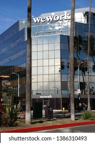 LOS ANGELES, Feb 21st, 2019: The WeWork office building on Hollywood Boulevard, on the Walk of Fame, against a blue sky and palm trees reflecting in its glass facade.