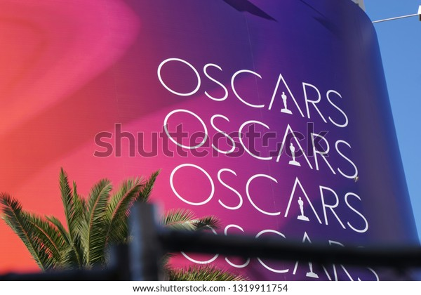 """LOS ANGELES, Feb 21st, 2019: The words """"Oscars"""" on a red background next to a palm tree, advertising the 91st Academy Awards Oscar ceremony held at the Dolby Theatre on Hollywood Boulevard."""