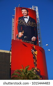 LOS ANGELES, FEB 23RD, 2017: Giant Oscar ad featuring host Jimmy Kimmel and a golden statue on a red background against the blue sky on the outside of the Hollywood and Highland mall.