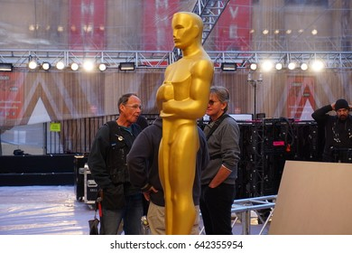 LOS ANGELES, FEB 23RD, 2017: Large, golden Oscar statue in the red carpet area for the 2017 Academy Awards, with host Jimmy Kimmel's marquee in the background, seen through protective plastic tarp.