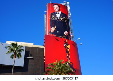 LOS ANGELES, FEB 24TH, 2017: Giant Oscar ad featuring host Jimmy Kimmel and a golden statue on a red background against the blue sky on the outside of the Hollywood and Highland mall.