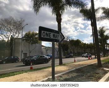 LOS ANGELES, Feb 28th, 2018: Wide shot of a One Way road sign underneath a palm tree, against a dramatic sky with clouds. On Santa Monica Boulevard in West Hollywood.