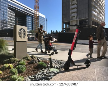 LOS ANGELES, Jan 4th, 2019: Pedestrians walk past an Uber Jump electric scooter that stands abandoned on the sidewalk at Constellation Boulevard in Century City, next to a Starbucks sign.