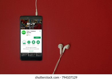 Los Angeles, January 11, 2018: Smartphone with Fiverr application in google play store on red background with earphones plugged in and copy space